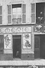 13 rue de la Grande Chaumière: Madame Charlotte Caron at the window above her crémerie (panel by Mucha to the left, by Slewinsky to the right)